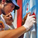 Andrea dipinge un murales per il Bilancio di Sostenibilità 2011-2012 Vodafone, sotto la guida attenta di Paolo Sha One Romano (Napoli Est, 2012).